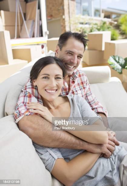 Retrato de casal sorridente agarrar no sofá na Entrada para Automóvel
