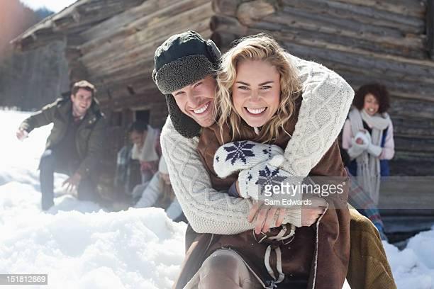 Porträt eines lächelnden Paares umarmen mit Freunden im Hintergrund