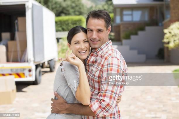 Retrato de casal sorridente na frente de casa nova