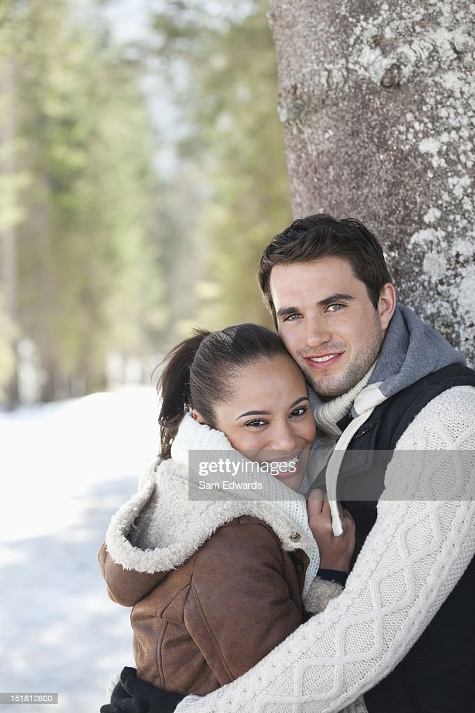 Portrait of smiling couple leaning against tree trunk in snowy woods : Stock Photo