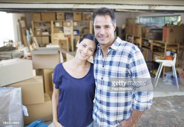Retrato de casal sorridente fora Garagem em caixas de cartão