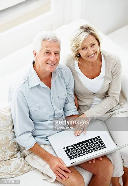 Portrait of smiling couple using laptop at home