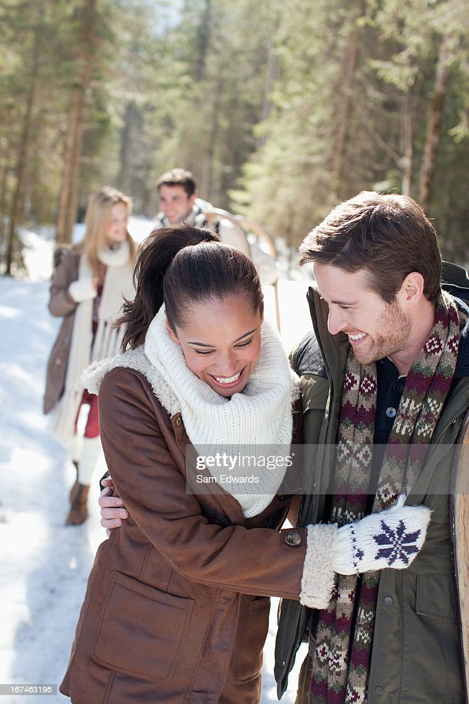 Portrait of smiling couple with sled in snowy woods : Stock Photo