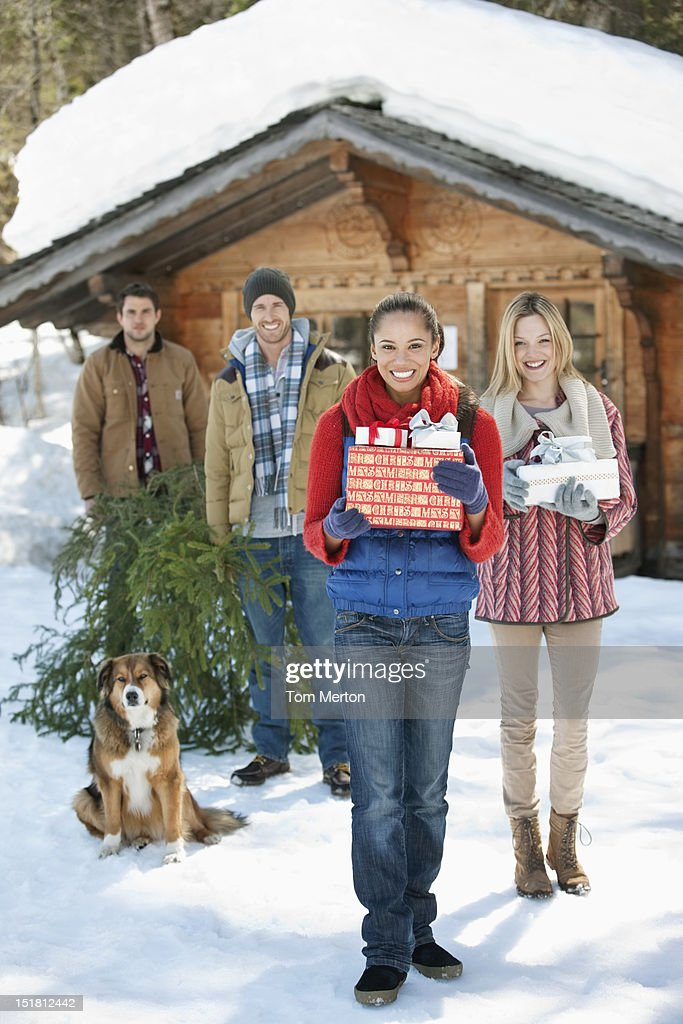 Portrait of smiling couples and dog with fresh cut Christmas tree and gifts in front of cabin : Stock Photo
