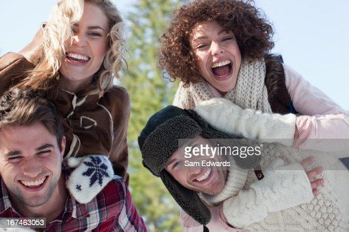 Portrait of smiling couples piggybacking : Stock Photo