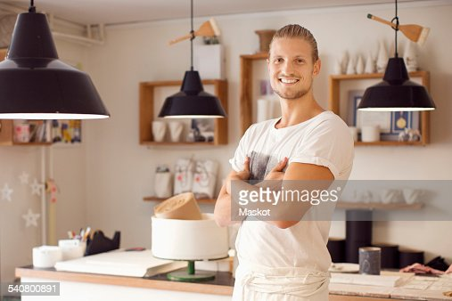 Portrait of smiling craftsperson standing with arms crossed in crockery workshop