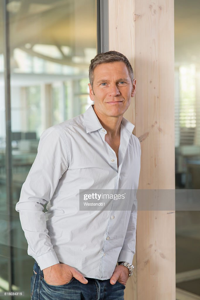 Portrait of smiling creative business man in front of glass pane