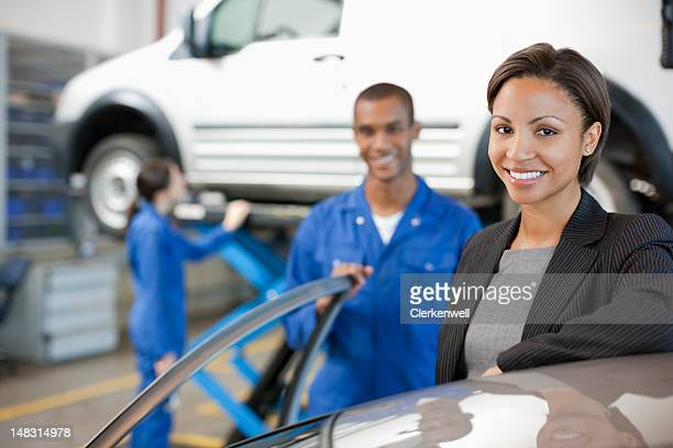 Portrait of smiling customer and mechanic in auto repair shop