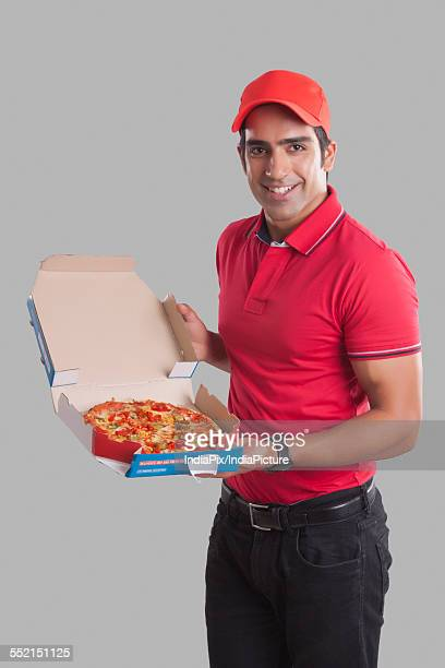 Portrait of smiling delivery man showing pizza against gray background