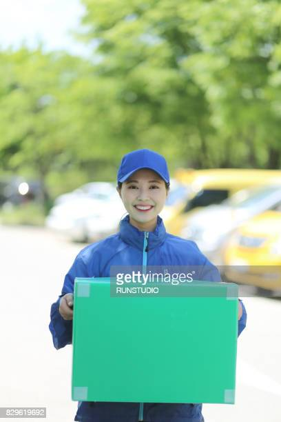Portrait of smiling delivery woman holding box