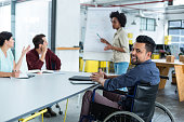 Portrait of smiling disabled business executive in wheelchair at meeting in office