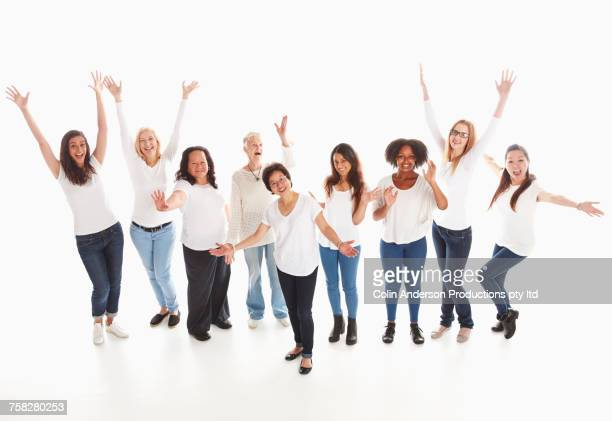 Portrait of smiling diverse women standing in a row celebrating