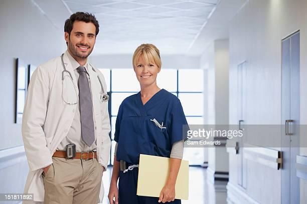 Retrato de sorrir médico e enfermeira no corredor de hospital