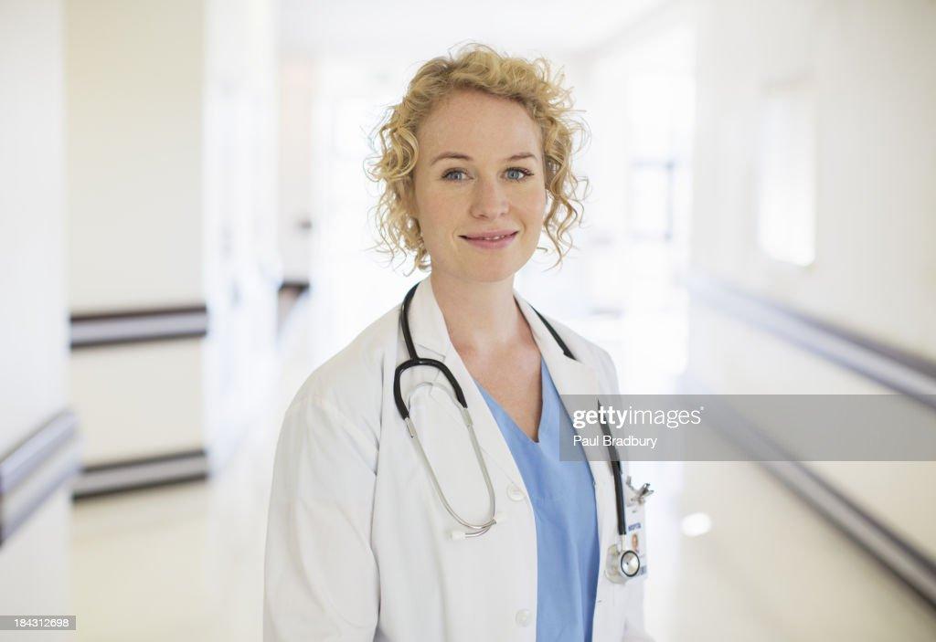 Portrait of smiling doctor in hospital corridor : Stock Photo