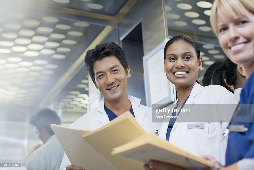 Portrait of smiling doctors and nurse with medical records : Stock Photo