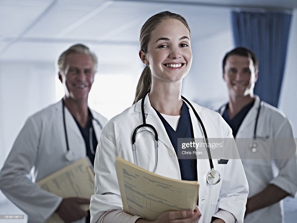 Portrait of smiling doctors holding medical records in hospital : Stock Photo