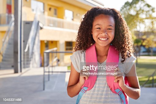 Portrait of smiling elementary school girl with her backpack : Stock Photo