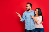 Portrait of smiling, embracing, excited, attractive couple pointing to copy space with forefinger over red background, having date