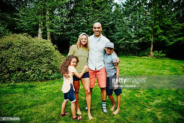 Portrait of smiling family embracing in backyard