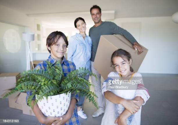 Retrato de uma família sorridente segurando pertences na nova casa