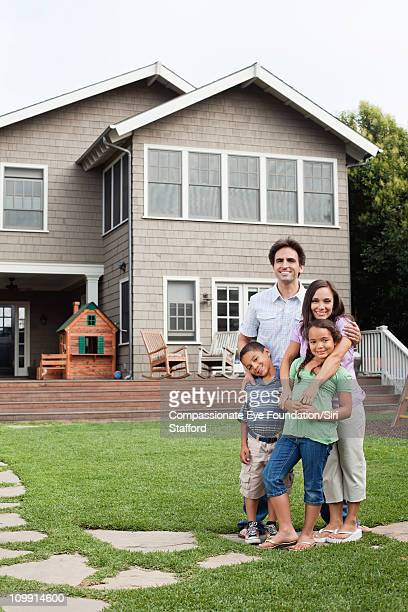portrait of smiling family in front of house