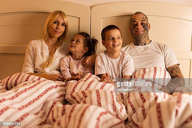 Portrait of smiling family in pajamas relaxing on the bed.