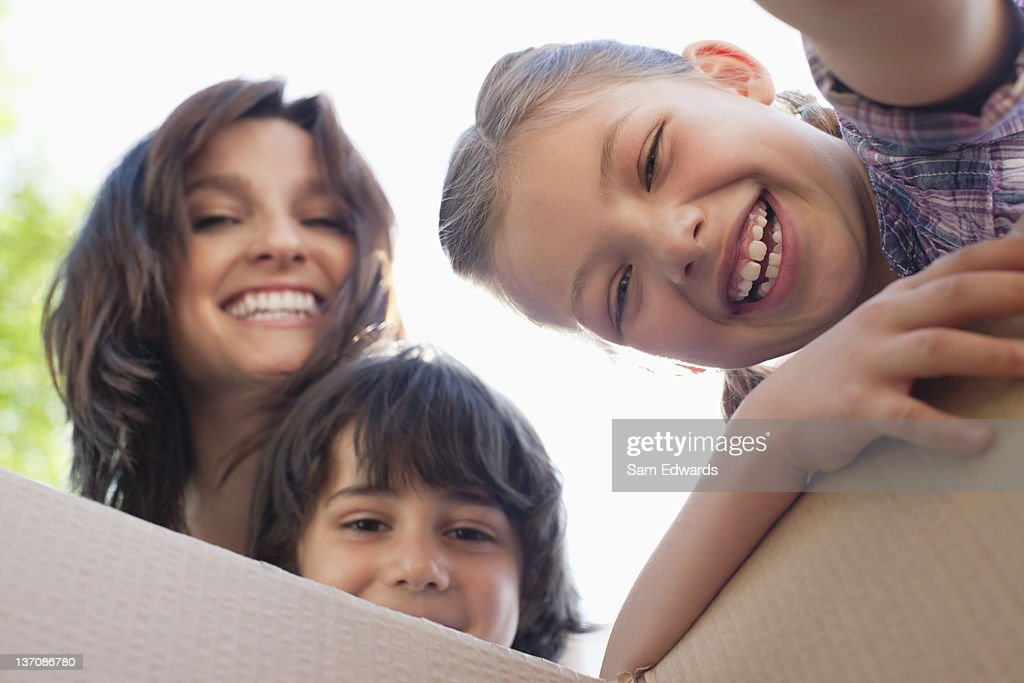 Portrait of smiling family looking into cardboard box : Stock Photo
