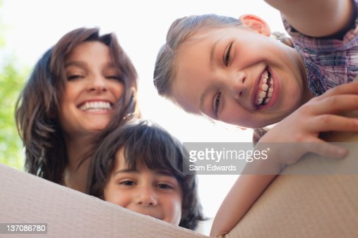 Portrait of smiling family looking into cardboard box : ストックフォト
