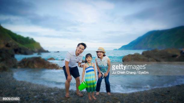 Portrait Of Smiling Family Standing Against Sea At Beach
