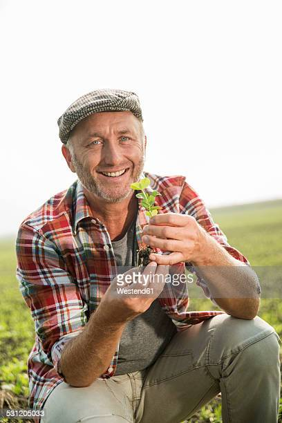 Portrait of smiling farmer holding a plant on a field