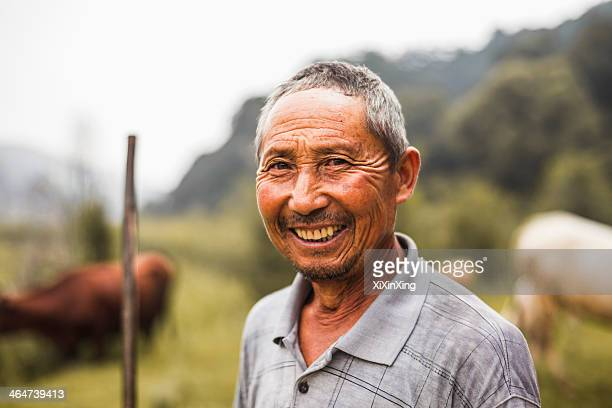 Portrait of smiling farmer with livestock in the background, rural China, Shanxi Province