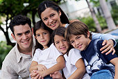 Portrait of smiling father and three children outdoors, tilt