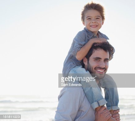 Portrait of smiling father carrying son on shoulders on beach