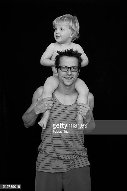 Portrait of smiling father carrying son on shoulders