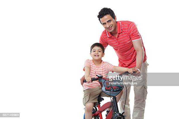 Portrait of smiling father teaching son to ride bicycle against white background