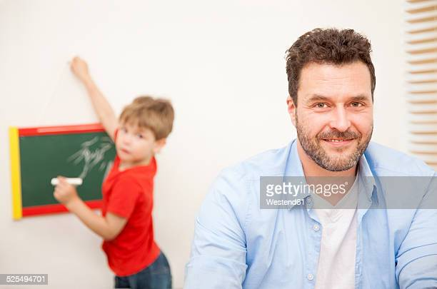 Portrait of smiling father with his little son in the background