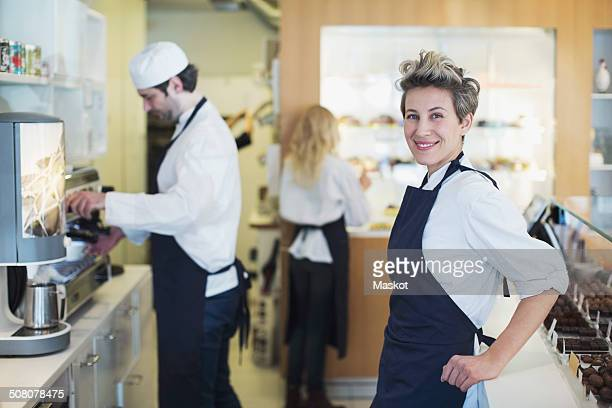 Portrait of smiling female cafe owner with colleagues working in background
