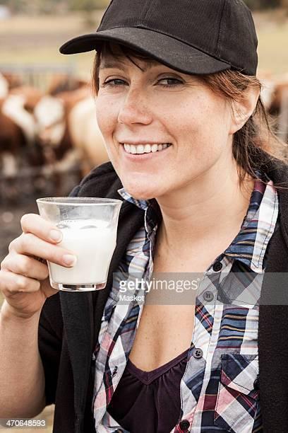 Portrait of smiling female farmer drinking milk in farm