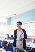 Portrait of smiling female teacher and elementary school children in classroom