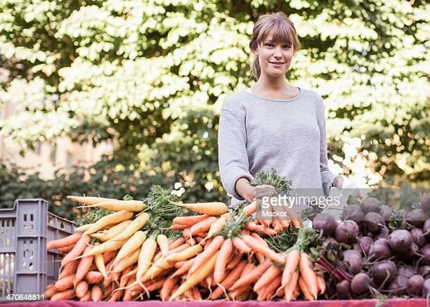 Portrait of smiling female vendor selling vegetables at market stall