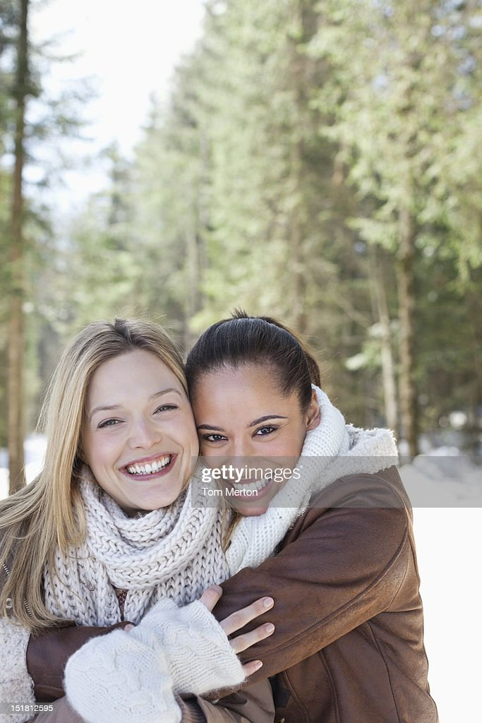 Portrait of smiling friends hugging in snowy woods : Stock Photo