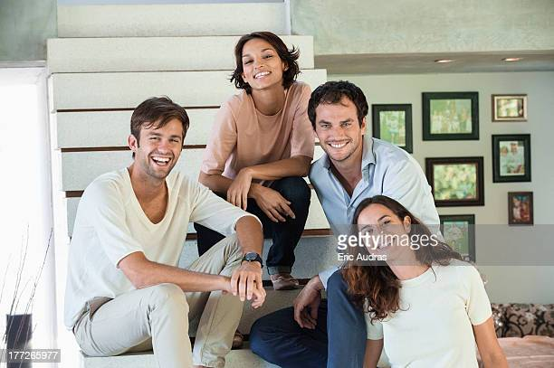 Portrait of smiling friends sitting on steps