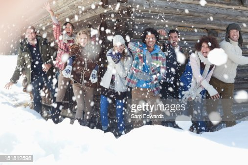 Portrait of smiling friends throwing snowballs in front of cabin