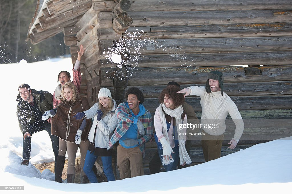 Portrait of smiling friends throwing snowballs in front of cabin : Stock Photo