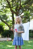 Portrait of smiling girl blowing bubbles in backyard