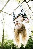 Portrait of smiling girl hanging upside down on jungle gym