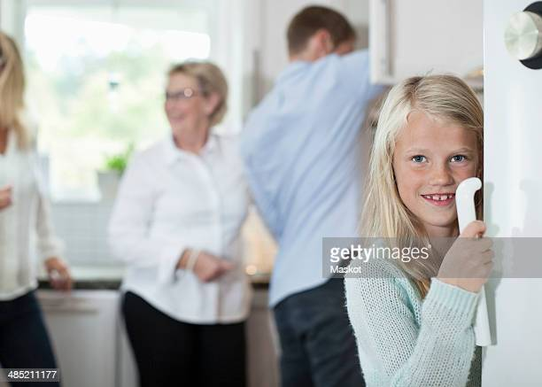 Portrait of smiling girl holding door handle with family in background at kitchen