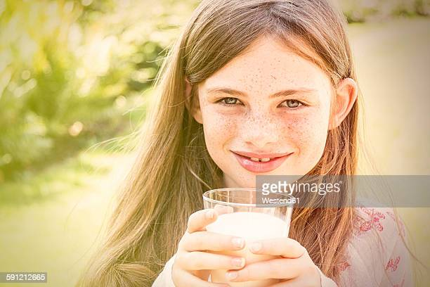 Portrait of smiling girl holding glass of milk
