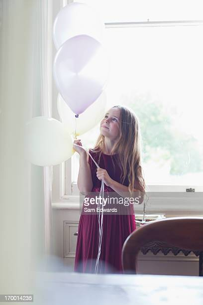 Portrait of smiling girl holding white balloons in front of window