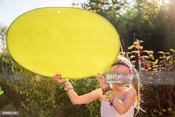 Portrait of smiling girl holding yellow speech balloon
